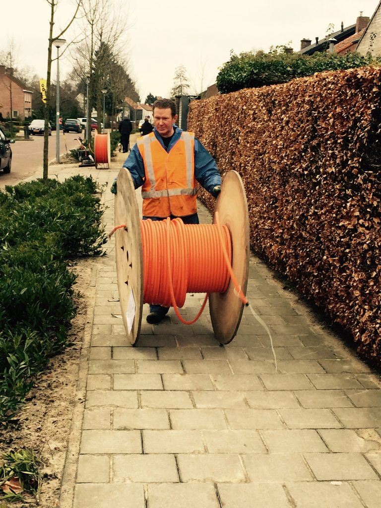 Man rolling spool of fiber down sidewalk